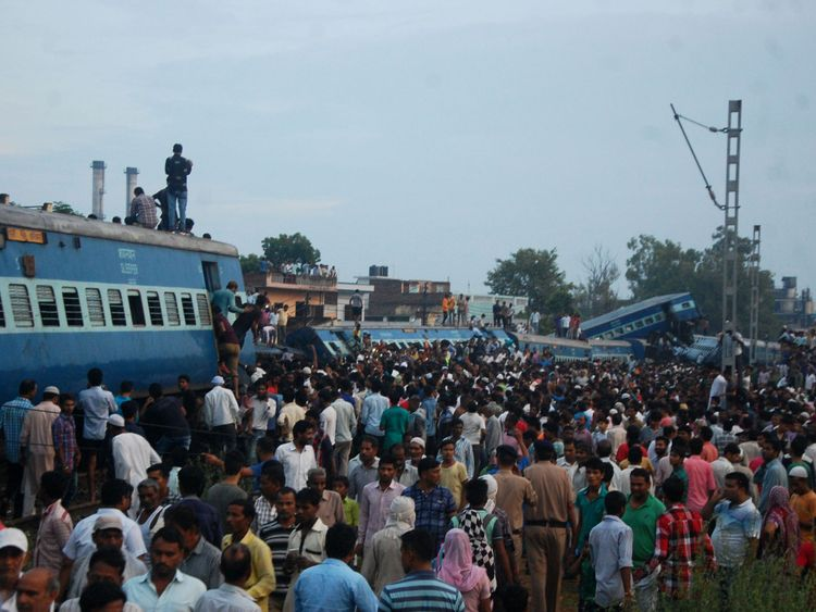 Local residents gather next to train carriages after an express train derailed near the town of Khatauli in the Indian state of Uttar Pradesh on August 19, 2017