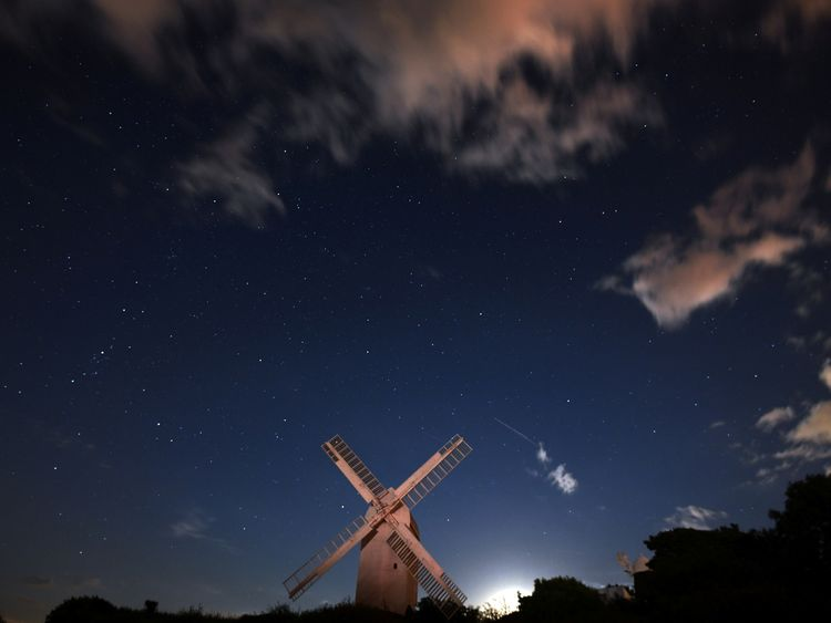 A meteor streaks past stars in the night sky above the Jill Windmill, during the Perseid meteor shower in Brighton, southern Britain, August 12, 2017