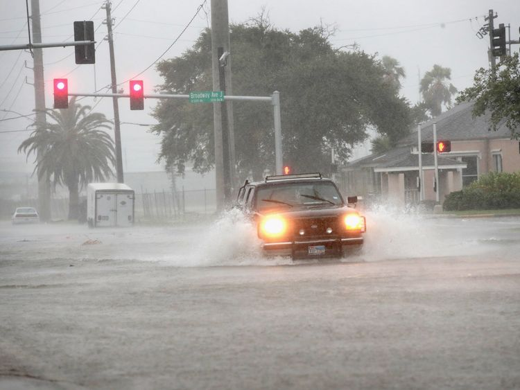 A vehicle navigates a street flooded by rain in Galveston, Texas