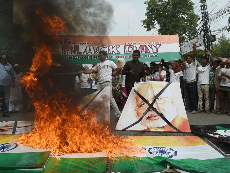 Activists of the Youth Forum of Kashmir burn Indian flags during a protest in Lahore on a day they call Black Day