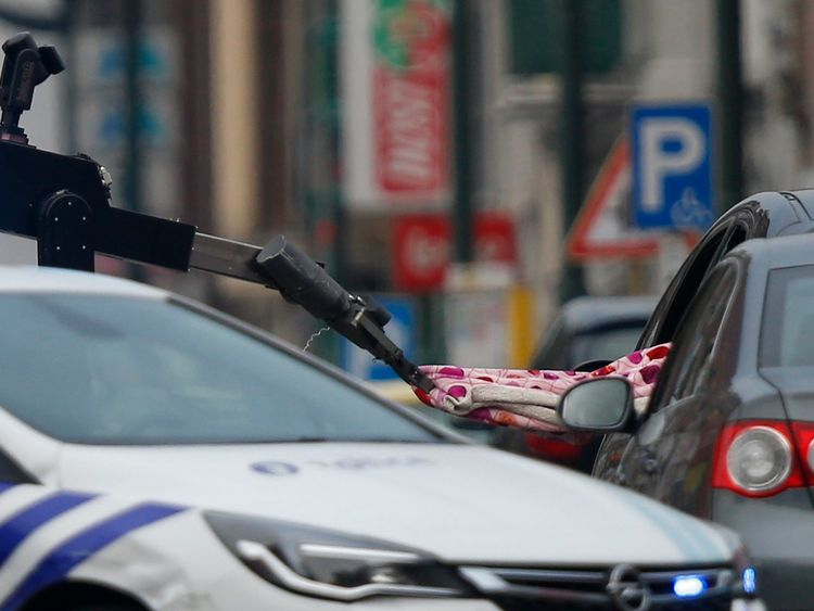 A robotic bomb detector probes the car