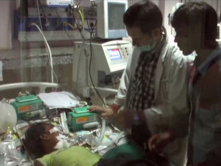 Medical staff tending to children in hospital beds, at the Baba Raghav Das Medical College Hospital