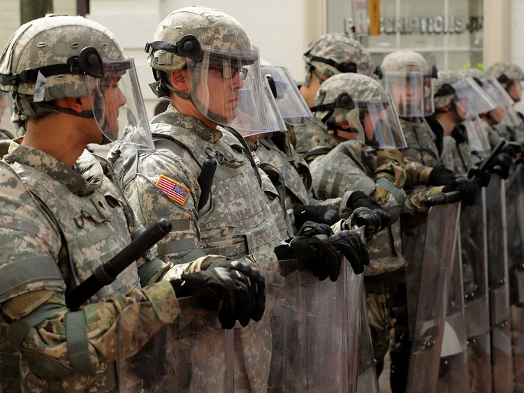 Members of the Virginia National Guard wear body armor and carry riot shields while standing guard on the pedestrian mall following violence at the United the Right rally August 12, 2017 in Charlottesville, Virginia