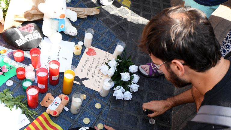 A man sets up a candle on the Las Ramblas street