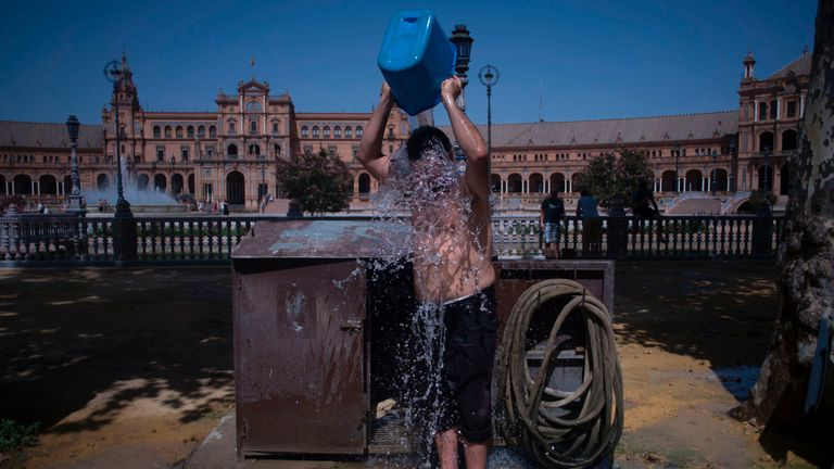 A man cools with a bucket of water next to Plaza de Espana in Sevilla during a heat wave, on July 13, 2017