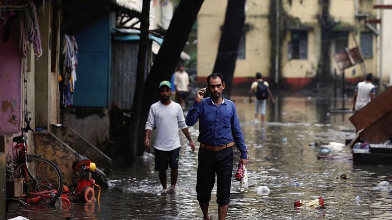 People walk through a partially flooded street at a residential area in Mumbai