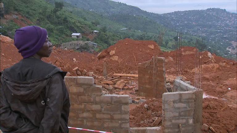 A resident looks down on the area where thousands of homes have been flattened and buried