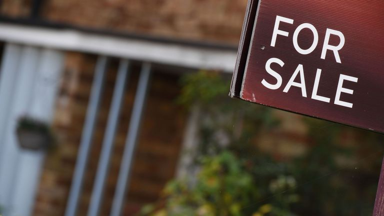 An estate agent's 'for sale' board stands outside a residential building in London