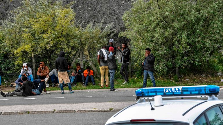 Police officers watch migrants at a roadside near Calais