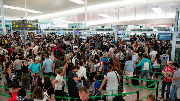 Passengers wait to pass through security at Barcelona's El Prat airport