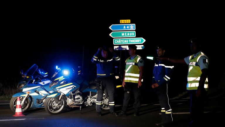 French gendarmes maintain a roadblock a certain distance from the scene where a car ploughed into the outdoor terrace of a pizzeria, killing a young girl and injuring several other people