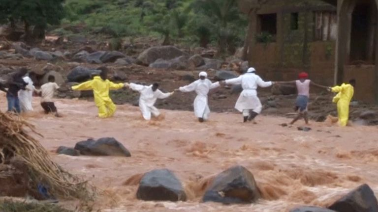 People wearing protective suits hold hands as they cross a river near one of the landslides