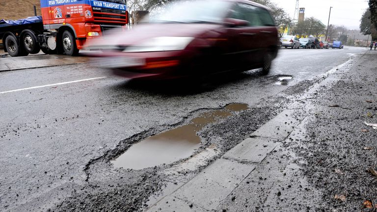 A car drives past a pothole