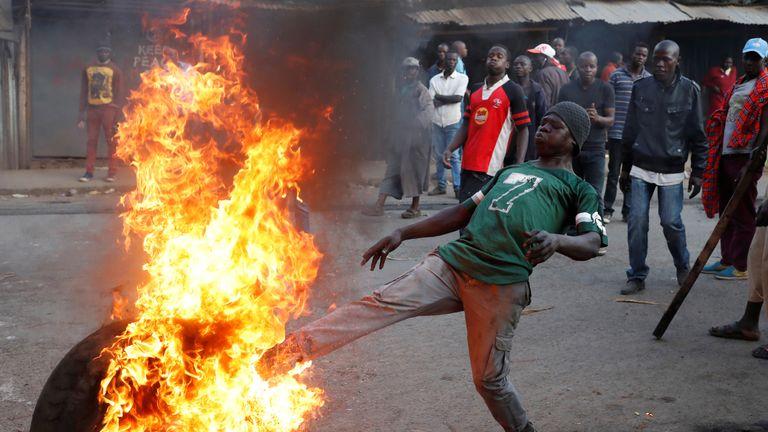 An opposition supporter kicks a flaming tyre in Kibera slum in Nairobi