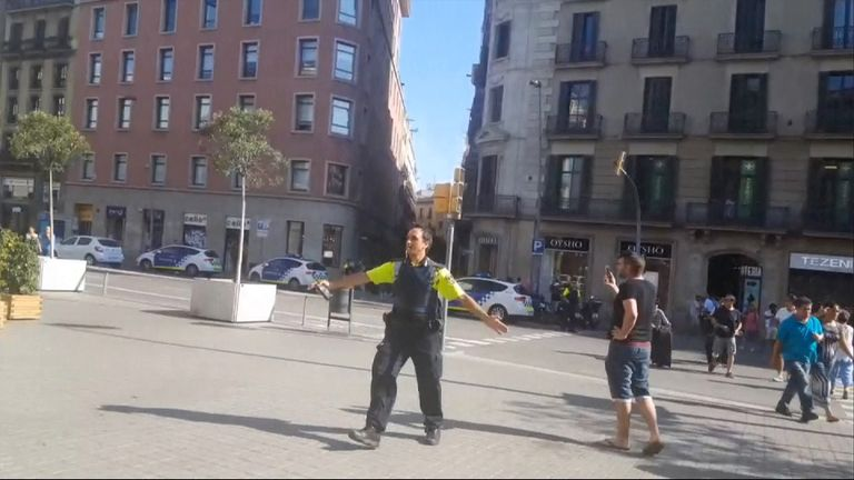 Authorities push people back on streets of Barcelona following an incident involving a van and a crowd