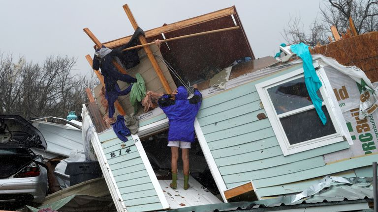A woman uses a coat hanger to try and retrieve an item from a destroyed house in Fulton, Texas