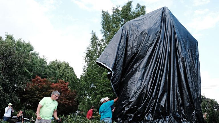 Workers replace the black tarp with which the City of Charlottesville covered the statue of Confederate General Robert E. Lee after John Miska (not shown) attempted to remove the covering in Charlottesville, Virginia, U.S., August 23, 2017