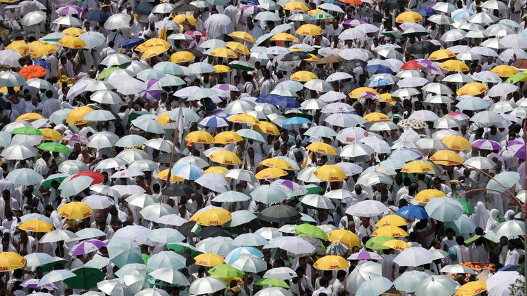 Muslim worshipers, carrying umbrellas to protect them from the scorching sun, gather for the noon prayer at Namirah mosque near Mount Arafat