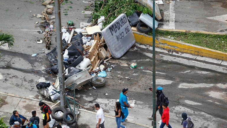 People walk past a street barricade