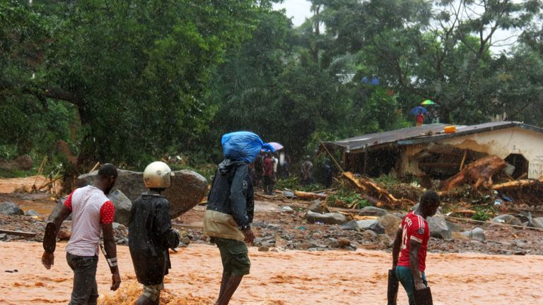 Residents walk through floodwaters past a damaged building in an area of Freetown on August 14, 2017, after landslides struck the capital of the west African state of Sierra Leone.
