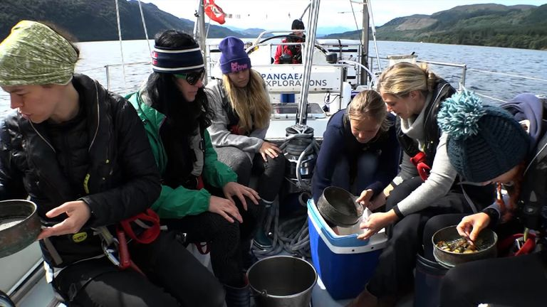 Members of the eXXpedition crew examine plastic debris from the sea