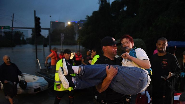 A woman is carried after being rescued from a hotel by boat due to the heavy flooding