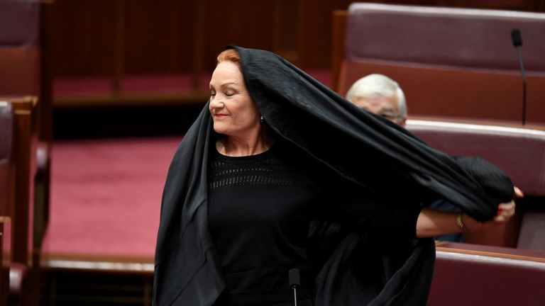 Australian One Nation party leader, Senator Pauline Hanson pulls off a burqa in the Senate chamber at Parliament House in Canberra