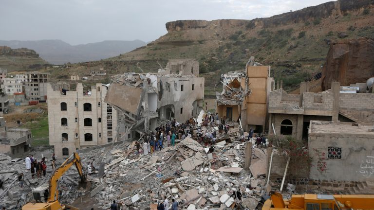 People search under the rubble of a house destroyed by a Saudi-led air strike in Sanaa