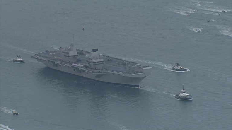HMS Queen Elizabeth surrounded by a flotilla of small ships