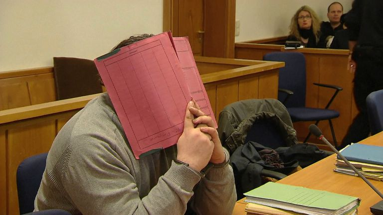 Niels Hoegel covers his face during a court appearance