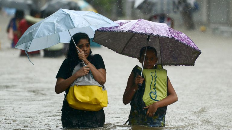 Indian girls wade through a flooded street during heavy rain in Mumbai