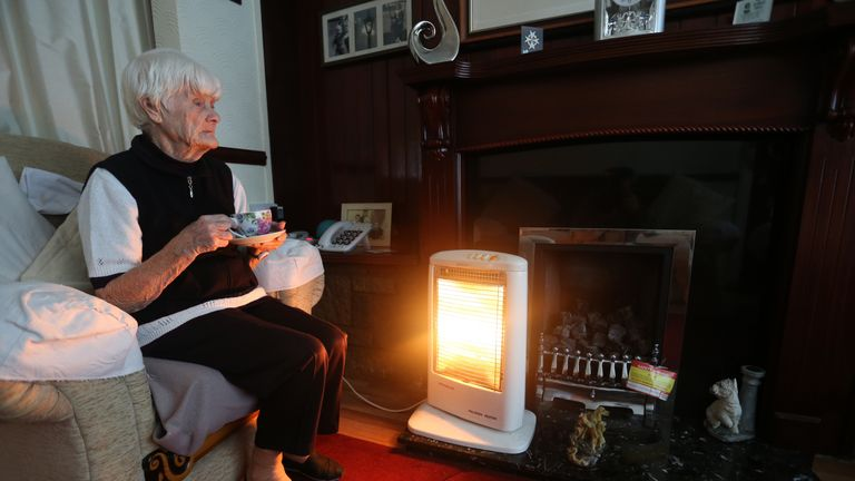 A generic stock photo of an elderly lady holding a cup of tea at home in Liverpool with her electric fire on.