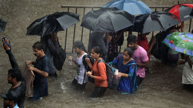People walk along a flooded street during heavy rain showers in Mumbai