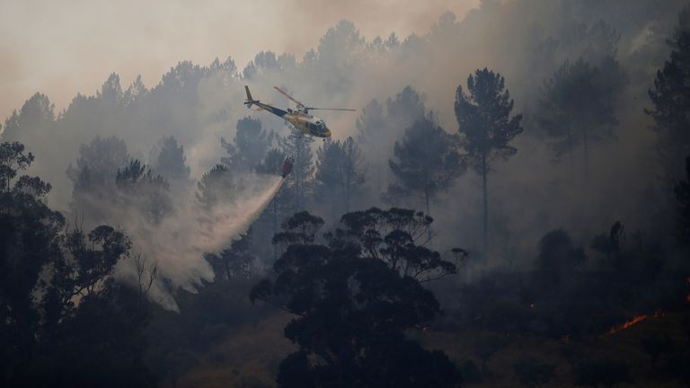 A firefighting helicopter drops water to extinguish a forest fire in Vila Velha de Rodao, near Castelo Branco, Portugal, July 27, 2017