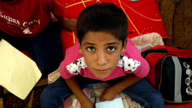 A displaced child from the Islamic State (IS) group's Syrian stronghold of Raqqa, poses for a photo as he attends the first day of the new school year at a camp for internally displaced people in Ain Issa on August 22, 2017