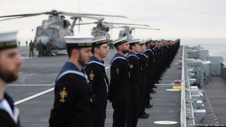 Sailors stand in line as the ship sails into harbour
