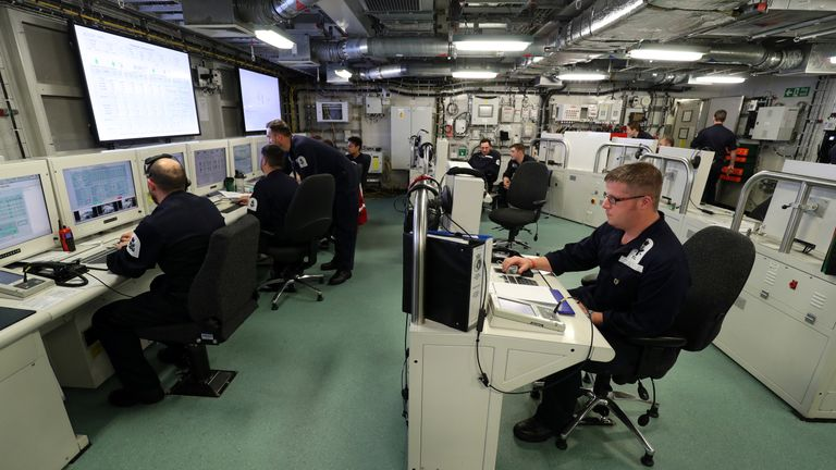 Crew members work in the ship control centre on board HMS Queen Elizabeth