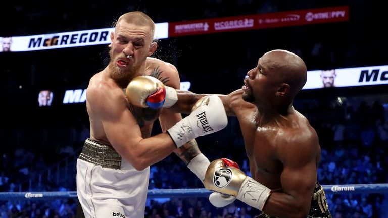 Mayweather throws a punch at McGregor as the fight gets under way