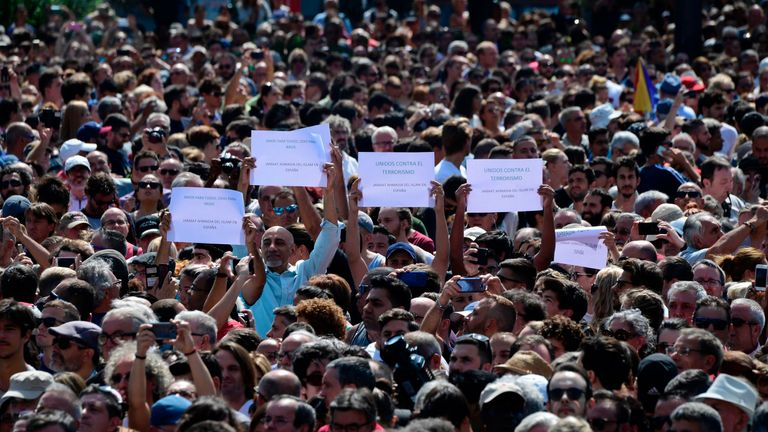 People brandish messages as they wait before a minute of silence for the victims of the Barcelona attack