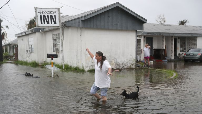 A woman and her dog leave their flooded house in Rockport