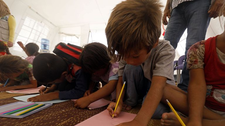 Displaced children from the Islamic State (IS) group's Syrian stronghold of Raqqa, attend the first day of the new school year at a camp for internally displaced people in Ain Issa on August 22, 2017