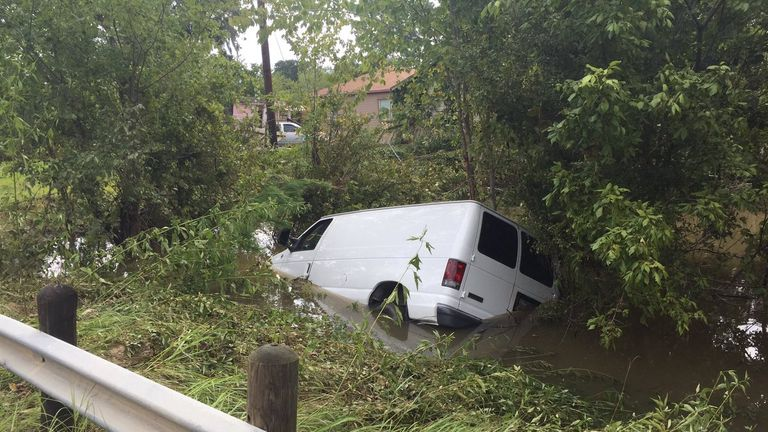 The van was swept off a bridge by floodwaters in Houston. Pic: @HCSOTexas