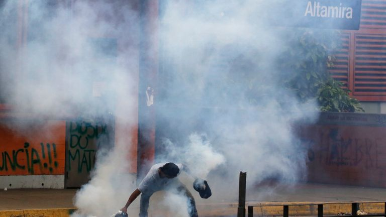 A demonstrator prepares to throw back a tear gas canister