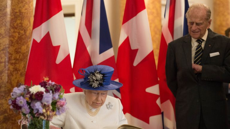 Queen Elizabeth II and Prince Philip, Duke of Cambridge sign the visitors book during their visit to Canada House on July 19, 2017 in London, England