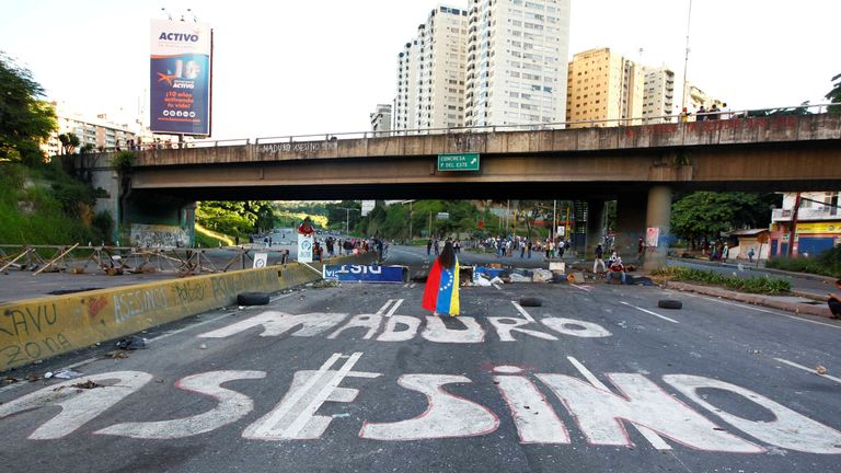 """Demonstrators walk on an empty highway with the words """"Maduro Assasin"""" painted on the surface after clashes broke out while the Constituent Assembly election was being carried out in Caracas, Venezuela, July 30, 2017. REUTERS/Christian Veron TPX IMAGES OF THE DAY"""