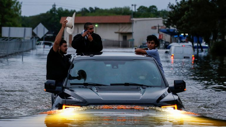 Residents use a truck to navigate through flood waters from Tropical Storm Harvey in Houston, Texas
