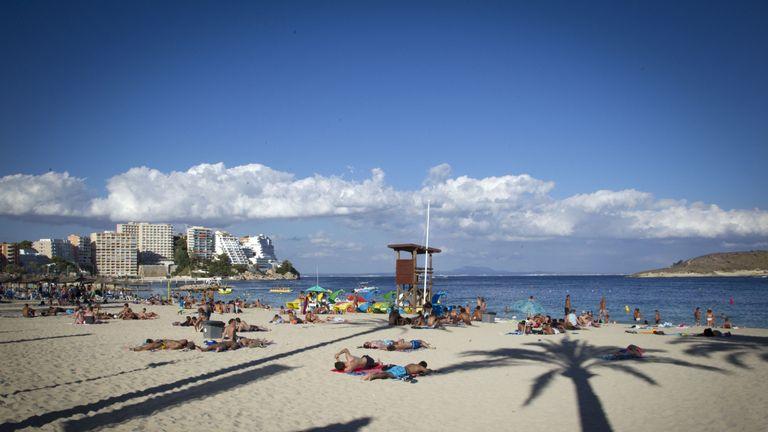 Tourists sunbath at Magaluf's beach in Calvia on Mallorca Island on August 10, 2015. AFP PHOTO/ JAIME REINA (Photo credit should read JAIME REINA/AFP/Getty Images)