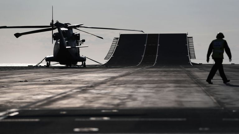 A Merlin helicopter next to the ski jump on the flight deck of HMS Queen Elizabeth