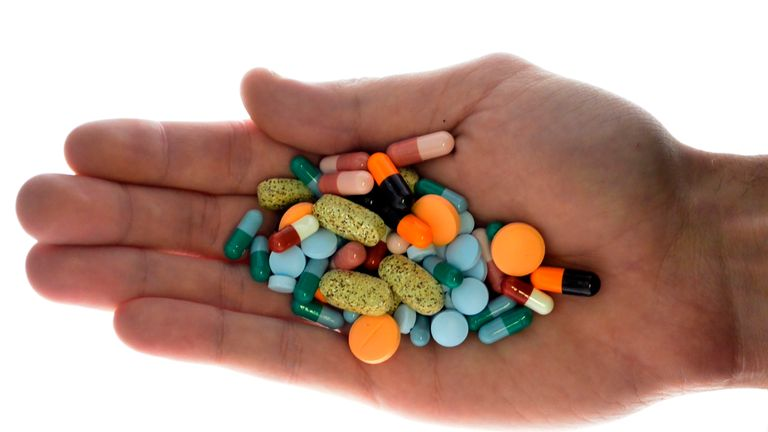 A person holds pharmaceutical tablets and capsules in this picture illustration taken in Ljubljana September 18, 2013