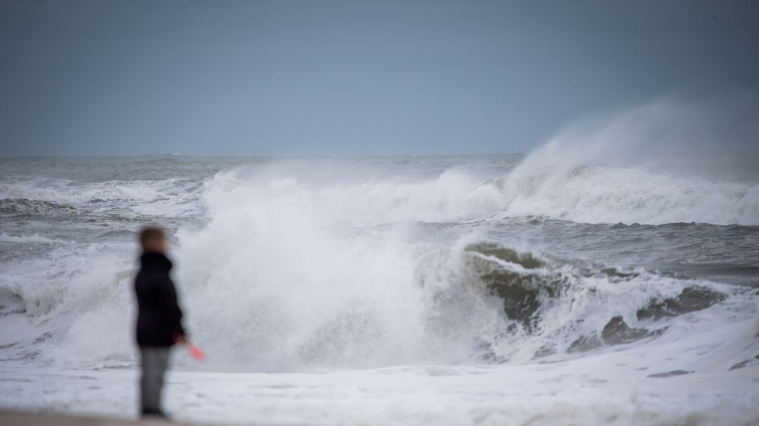 People walk along the beach as high waves produced by Hurricane Jose crash along the shore on September 20, 2017 at Long Island's Smith's Point Beach in Shirley, New York